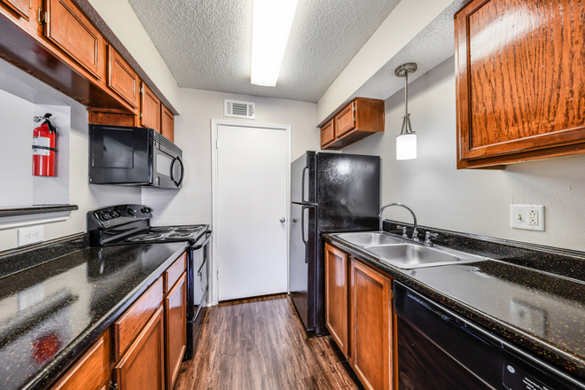 Madrid Floor Plan: Kitchen with Black Appliances and Full-Size Washer/Dryer Connections