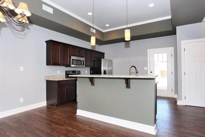 Open kitchen with stainless appliances - End-Unit Craftsman Style Townhouse in Cornerstone