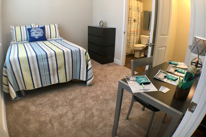 Bedroom- Furnished with desk, bed, dresser - Seahawk Cove - Now Leasing for Fall 2020 Apartments